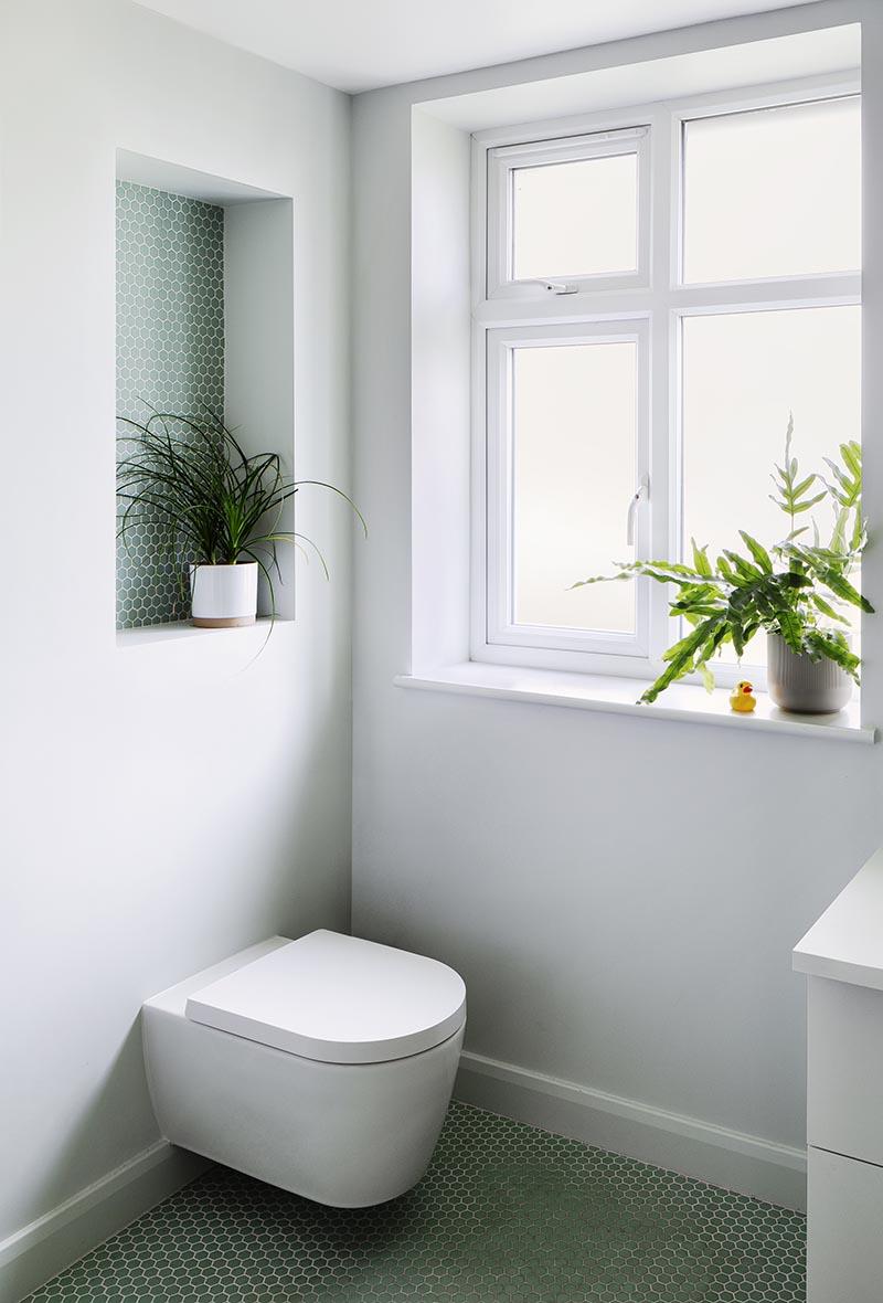 Cette salle de bain moderne dispose d'une étagère encastrée, assez grande pour afficher une plante, et comprend de petites tuiles à six pans avec coulis blanc. Il contribue également à ajouter une touche de couleur au mur gris uni et attire l'attention des toilettes en dessous. #BathroomShelf #BathroomIdeas #RecessedShelf #PennyTile #BathroomDesign