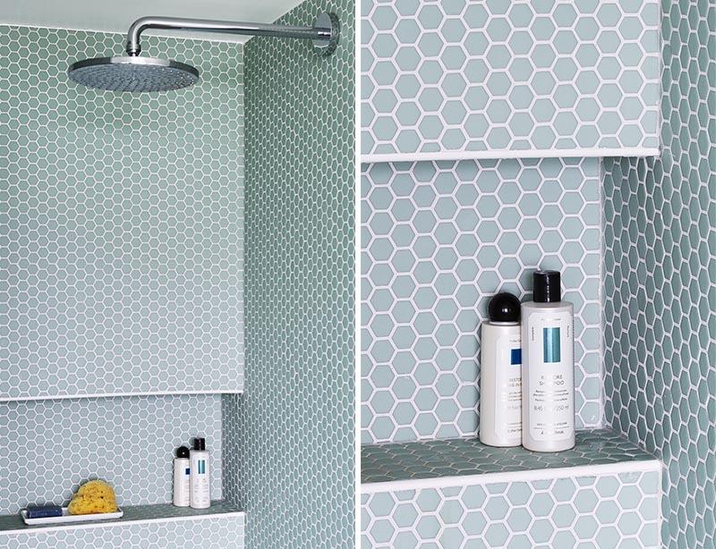 Cette salle de bain moderne dispose d'une douche bordée de carreaux de penny hexagonaux bleu clair, et dispose également d'une niche de douche intégrée. #ShowerNiche #PennyTile #ShowerIdeas #BathroomIdeas