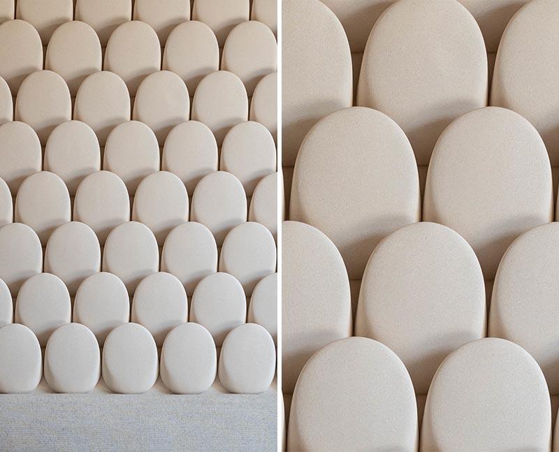 Cette chambre moderne dispose d'un mur d'accent accrocheur, qui ressemble à de petites pierres arrondies, et contribue à ajouter de la texture à la pièce. #AccentWall #ModernBedroom #SculpturalWall #BedroomDesign