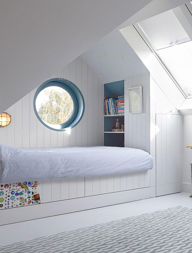 Cette chambre d'enfant moderne a un lit intégré qui a été rentré à une extrémité de la pièce, créant une aire de jeux ouverte qui est adoucie par l'utilisation d'un tapis moderne, et comprend un stockage sous la forme d'un placard et d'une étagère. #KidsBedroom #ModernKidsBed #BuiltInBed #Interiors #BedroomDesign