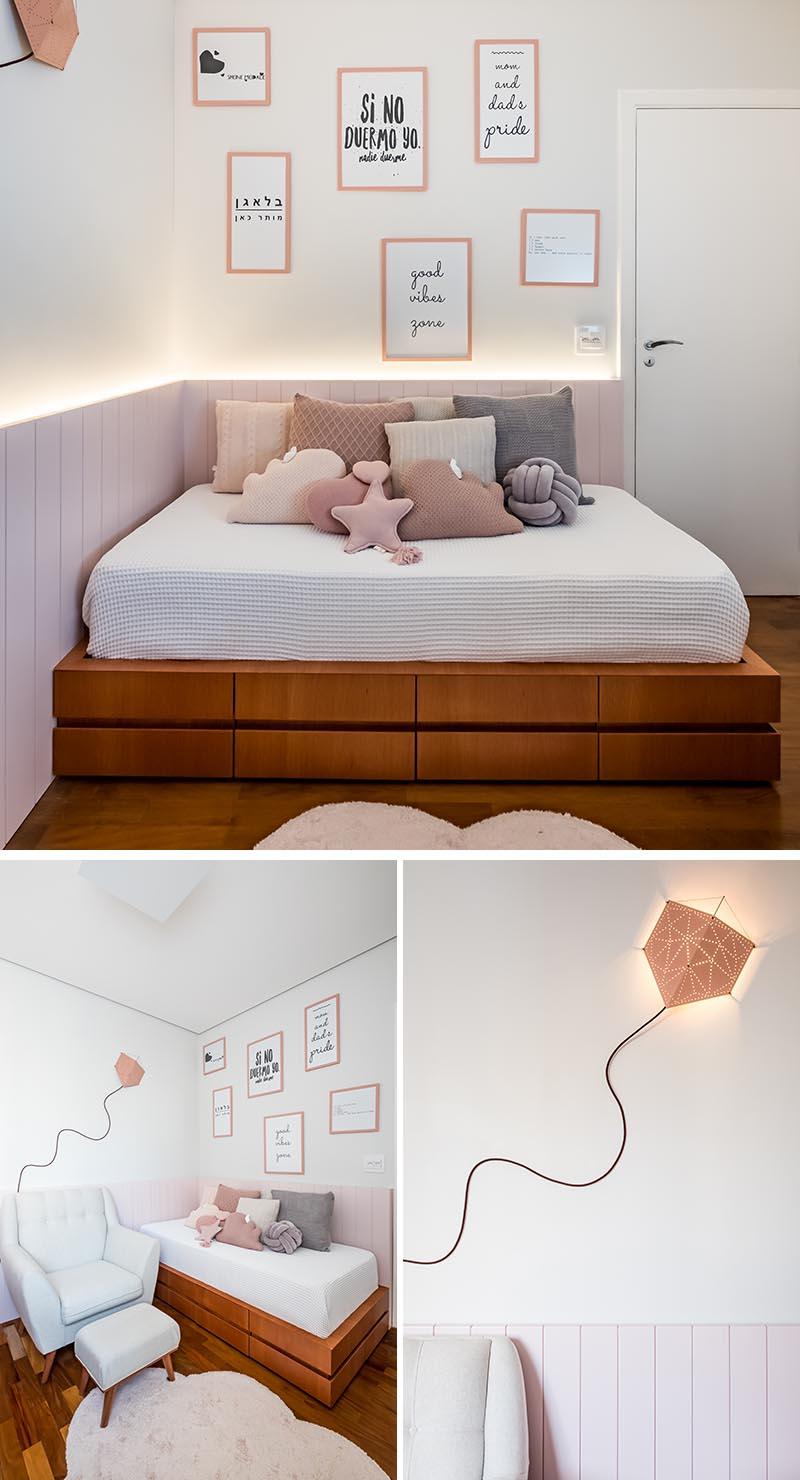 Une palette de roses doux et de bois naturel Jequitibá a été utilisée dans cette pépinière moderne, tandis que les boiseries avec éclairage indirect caché contribuent à créer une sensation de chaleur. En entrant dans la pépinière, il y a un lit de jour personnalisé avec des tiroirs de rangement en dessous, et une lampe de cerf-volant sur le mur ajoute une touche créative et ludique. #ModernNursery #PinkNursery #GirlsBedroom #InteriorDesign #Interiors #NurseryRoom #BabyRoom