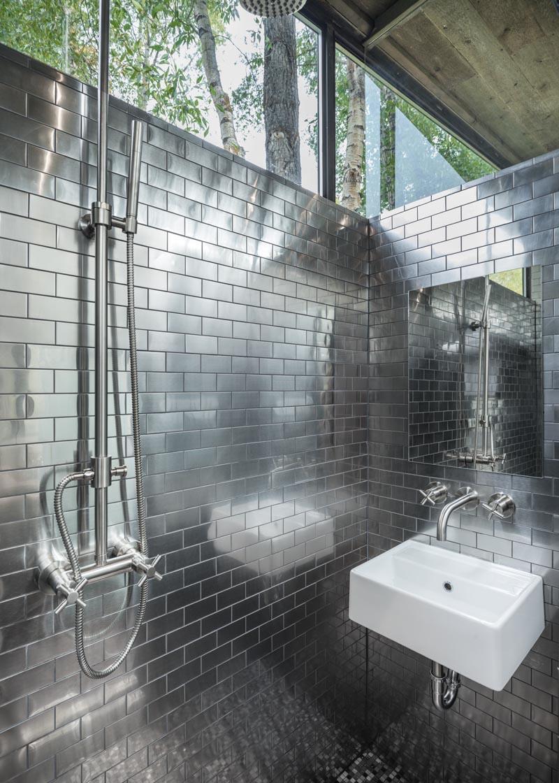 Cette petite maison a une salle de bain pleine grandeur avec des tuiles de métro en acier inoxydable qui couvrent les murs et des fenêtres qui rencontrent le toit. #Salle de bain #TinyHouseBathroom #TinyHouse #St StainlessSteelTiles