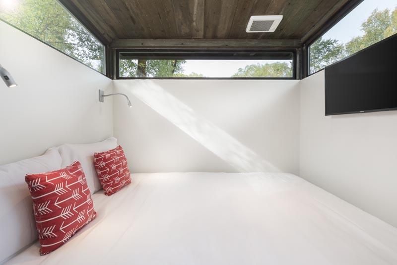 De longues fenêtres étroites enveloppent la chambre dans cette petite maison, tandis qu'une paire d'appliques fournit de la lumière la nuit. #TinyHouse #TinyHome #Chambre