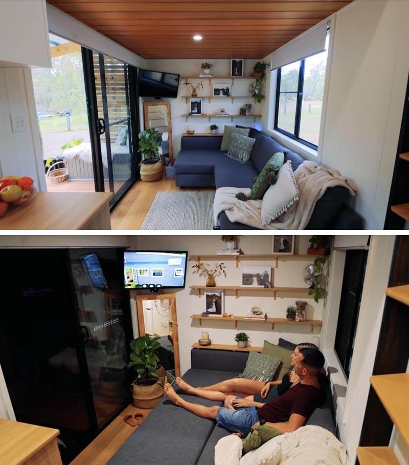En franchissant les portes coulissantes de cette petite maison moderne, vous êtes immédiatement dans le salon qui comprend un mur d'étagères en bois, et un canapé de taille standard avec rangement caché et une section coulissante qui le transforme en un endroit confortable à regarder la télé. #TinyHouse #TInyHouseLivingRoom #SmallLiving