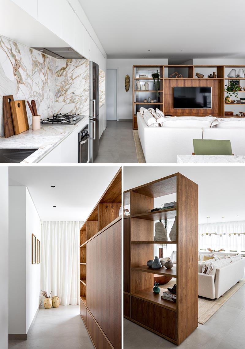 Ce séparateur de pièce moderne, en bois Freijó, crée un espace pour accueillir les résidents et les visiteurs avant d'atteindre le plan d'étage ouvert du salon, de la cuisine et de la salle à manger. Du côté du salon, le rayonnage offre un espace désigné pour le téléviseur dans le salon, ainsi qu'un rangement sous forme d'étagères et de tiroirs. #RoomDivider #WoodRoomDivider #WoodPartition #WoodShelving #LivingRoom #InteriorDesign #Interiors