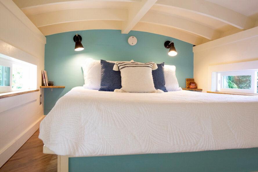 une chambre avec plafond incurvé, mur d'accent bleu et literie blanche
