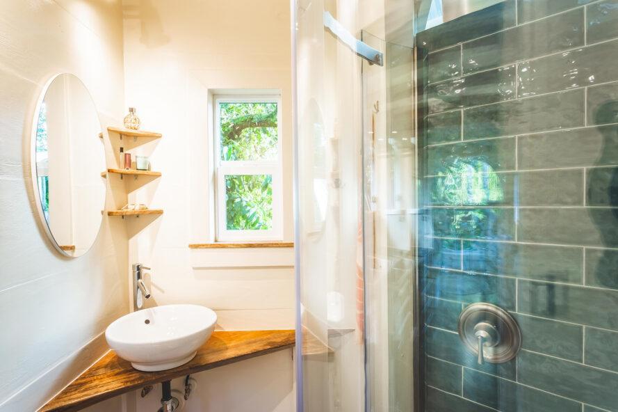 une salle de bain avec lavabo d'angle et étagères, et une douche carrelée en bleu
