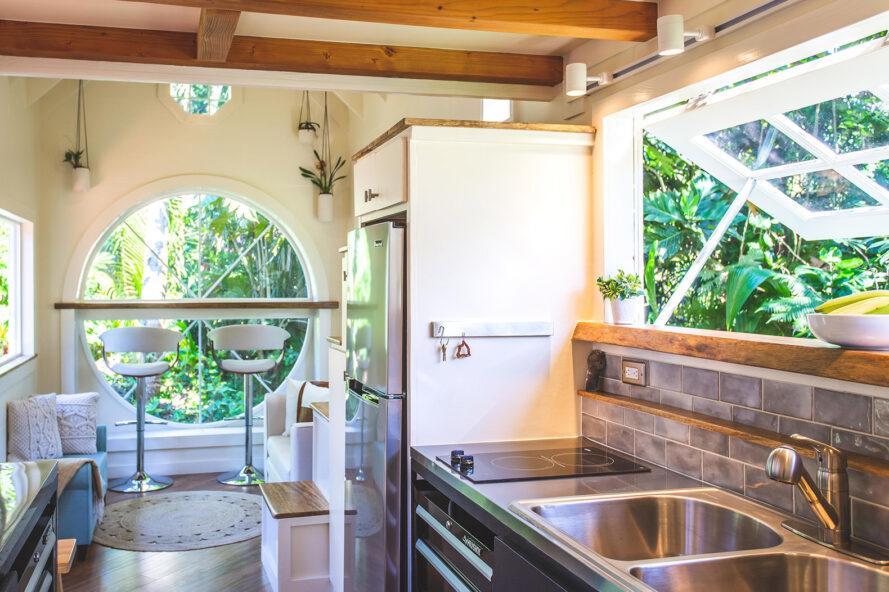 un coin cuisine avec comptoirs en acier et deux fenêtres, l'une rectangulaire et au-dessus de l'évier, l'autre circulaire et sur le mur opposé