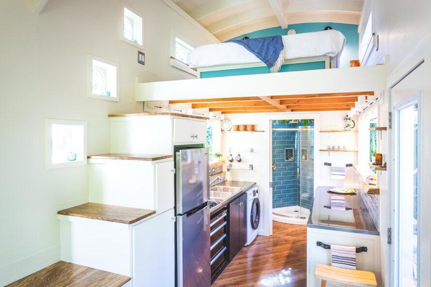 intérieur d'une petite maison, avec des accents blancs et bleus. un réfrigérateur et un coin cuisine sont nichés sous un escalier menant à une mezzanine