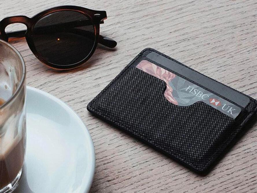 porte-cartes en cuir végétalien près d'une tasse de café et de lunettes de soleil