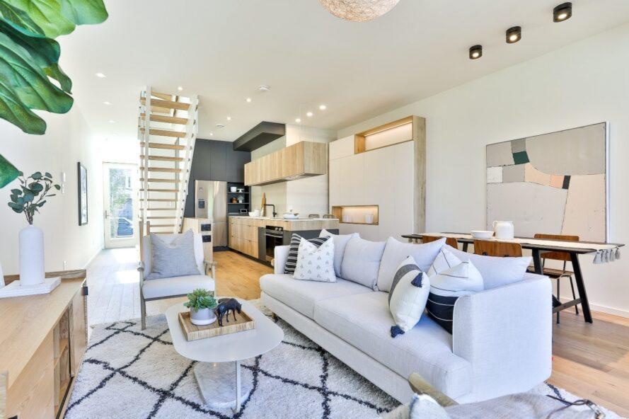 espace de vie principal avec canapé blanc et tapis imprimé