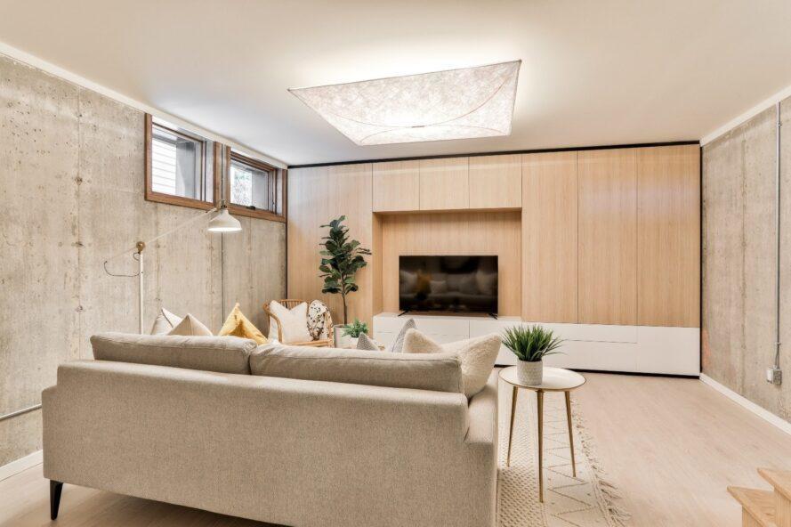 canapé gris clair près d'un mur lambrissé avec télévision à écran plat