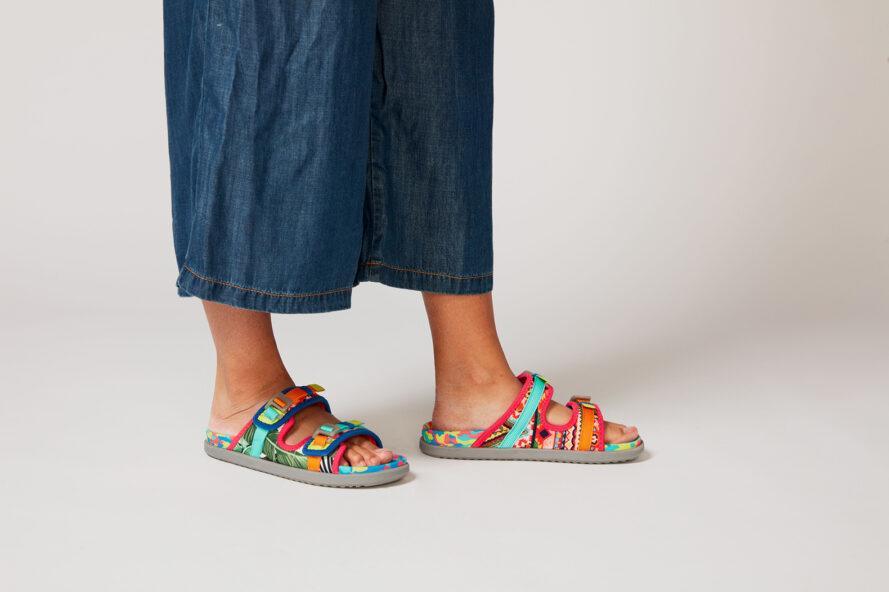 une personne en jean bleu lâche portant une paire de sandales multicolores, les deux pieds au sol
