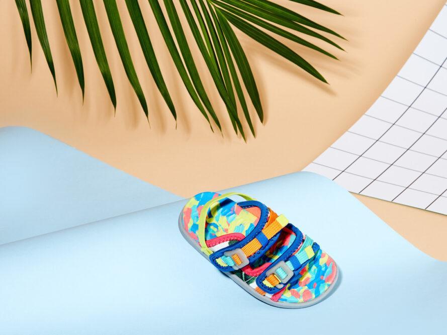 une sandale multicolore appuyée contre un fond de papier bleu ondulé, avec une feuille verte derrière elle
