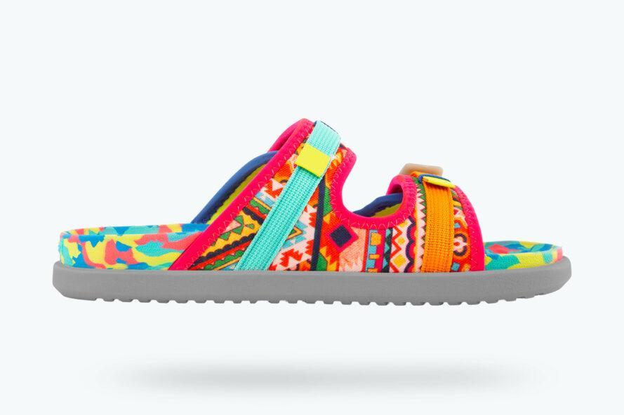 une sandale multicolore avec des accents roses, orange et bleus sur un fond blanc