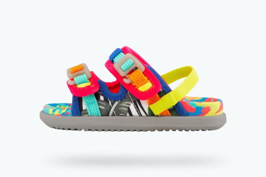 une sandale multicolore de taille enfant avec des accents roses, orange et bleus avec une bride de talon jaune sur un fond blanc