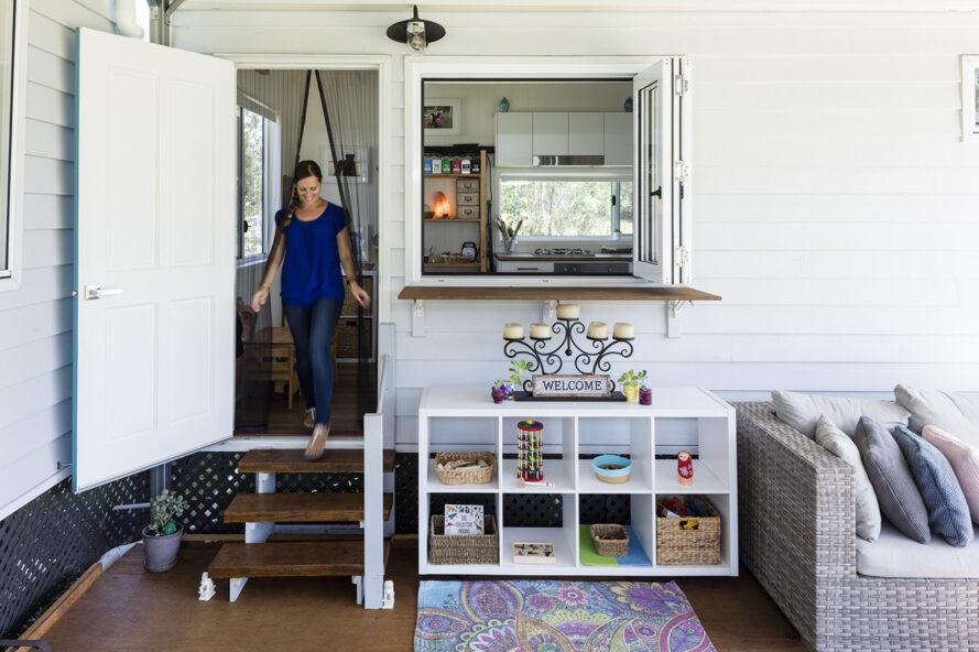 une femme en chemise bleue et un jean marchant dehors sur le porche via un petit escalier.  à droite de la porte se trouve une fenêtre donnant sur la maison.