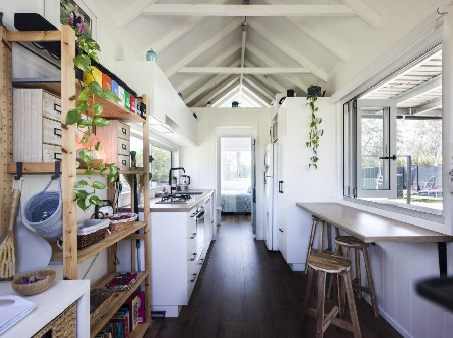une cuisine avec armoires et appareils blancs.  une étagère est visible à gauche, et à droite est un coin salon qui regarde par une fenêtre.