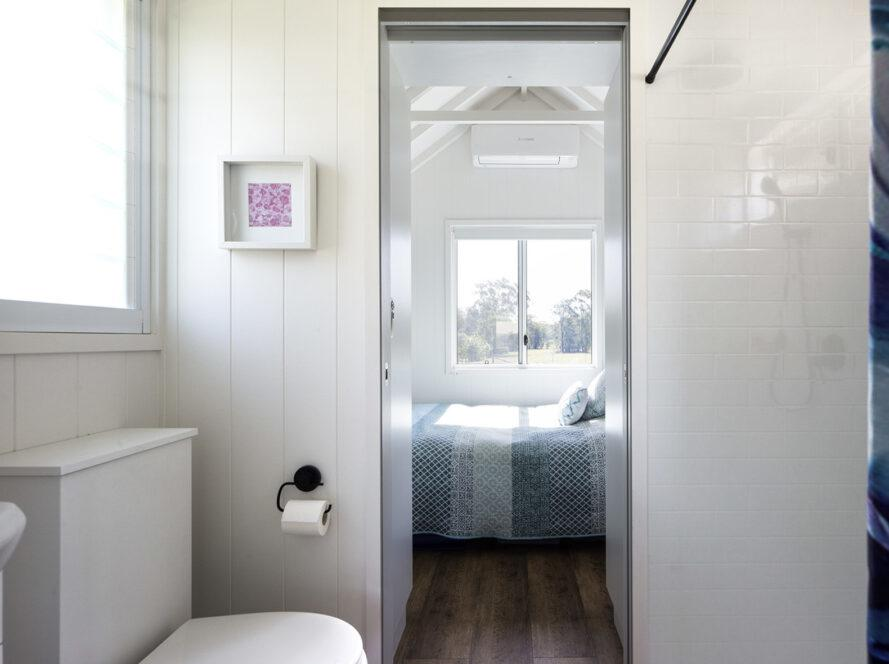 une salle de bain avec un WC blanc visible à gauche.  la porte de la salle de bain est ouverte et donne sur une chambre avec une couette à motifs bleus et des fenêtres.