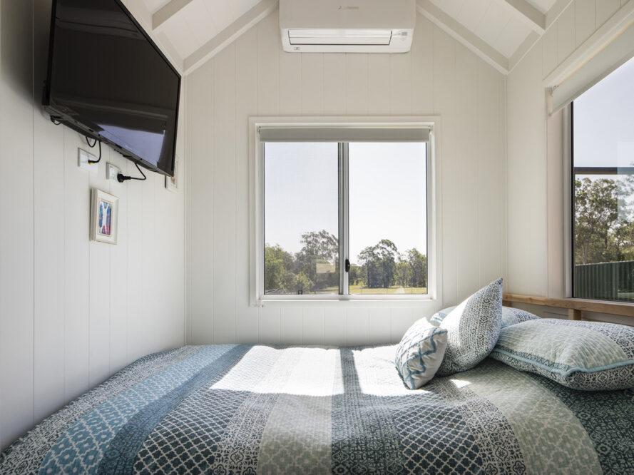 une chambre avec une couette à motifs bleus et des fenêtres donnant sur la verdure.  à gauche, un téléviseur est fixé au mur.