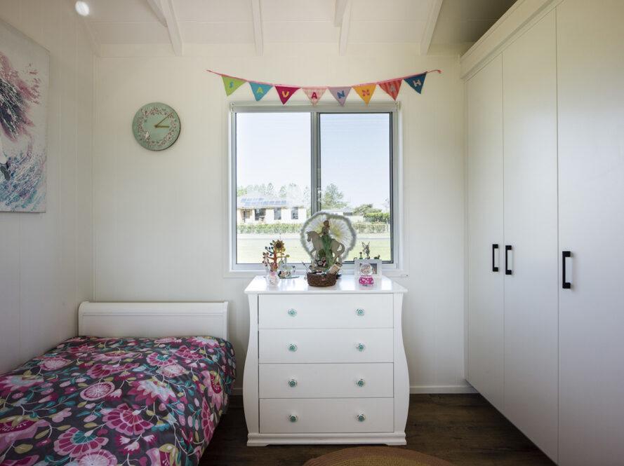 """une chambre d'enfant.  à gauche, un lit à motifs de fleurs roses couvre un lit.  au-dessus du lit est une horloge bleu-vert, et à gauche du lit est une œuvre d'art abstrait.  au milieu du mur est une commode blanche avec des décorations sur le dessus et des fenêtres au-dessus de la commode.  à gauche, de grandes armoires de rangement blanches.  une bannière au-dessus des fenêtres lit """"Savane."""""""