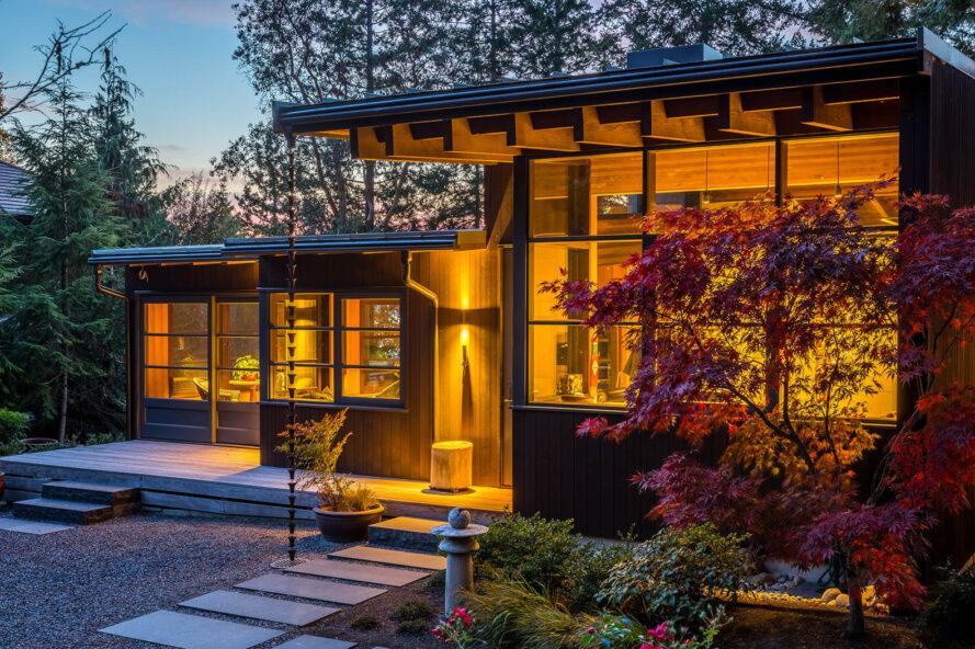une maison à un étage éclairée de l'intérieur et entourée par la nature
