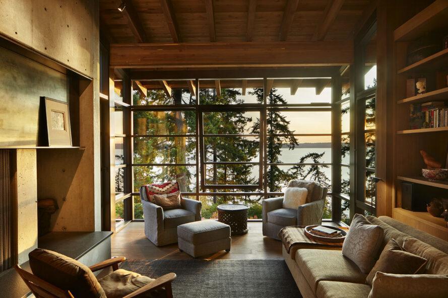 l'intérieur du salon d'une maison avec des fenêtres et des chaises du sol au plafond et un canapé remplissant la pièce