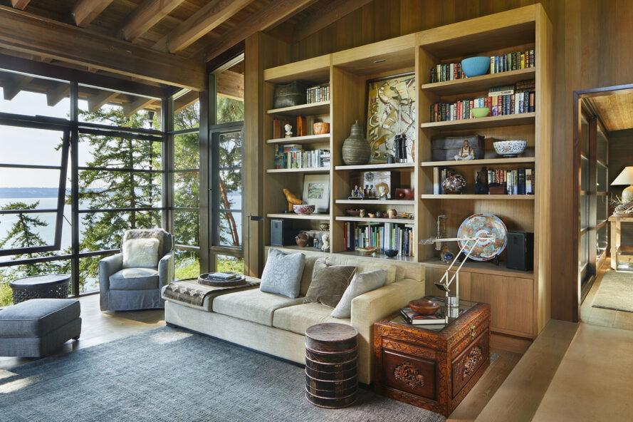 un salon avec des baies vitrées, un mur de bibliothèque, des chaises et un canapé remplissant la pièce