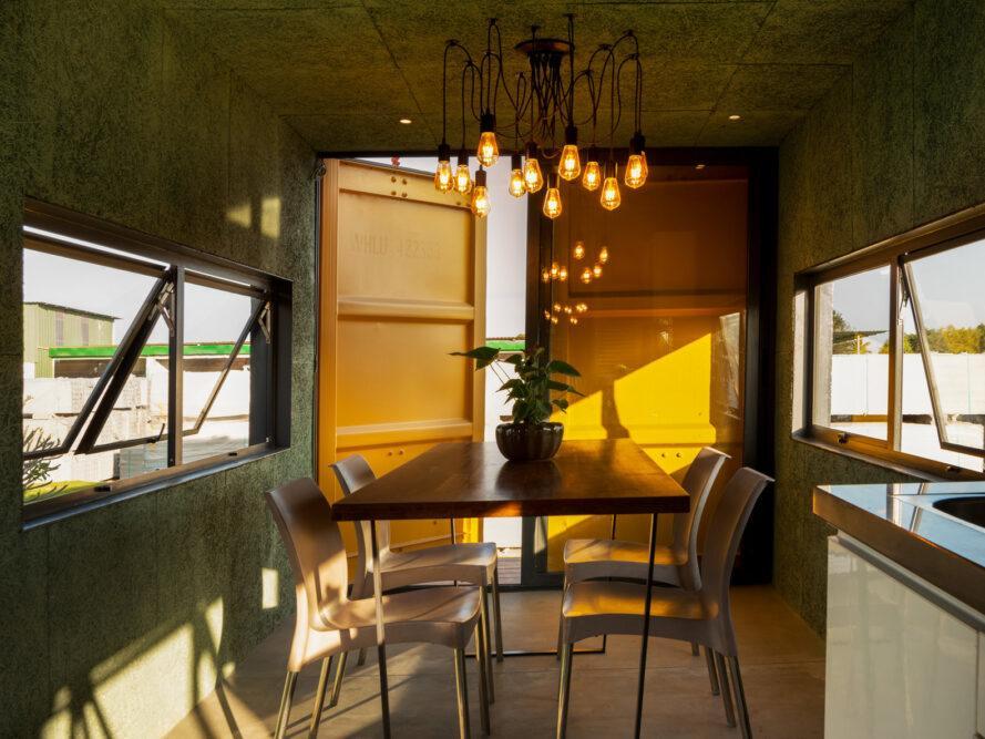 chambre jaune avec petite table à manger sous un lustre moderne