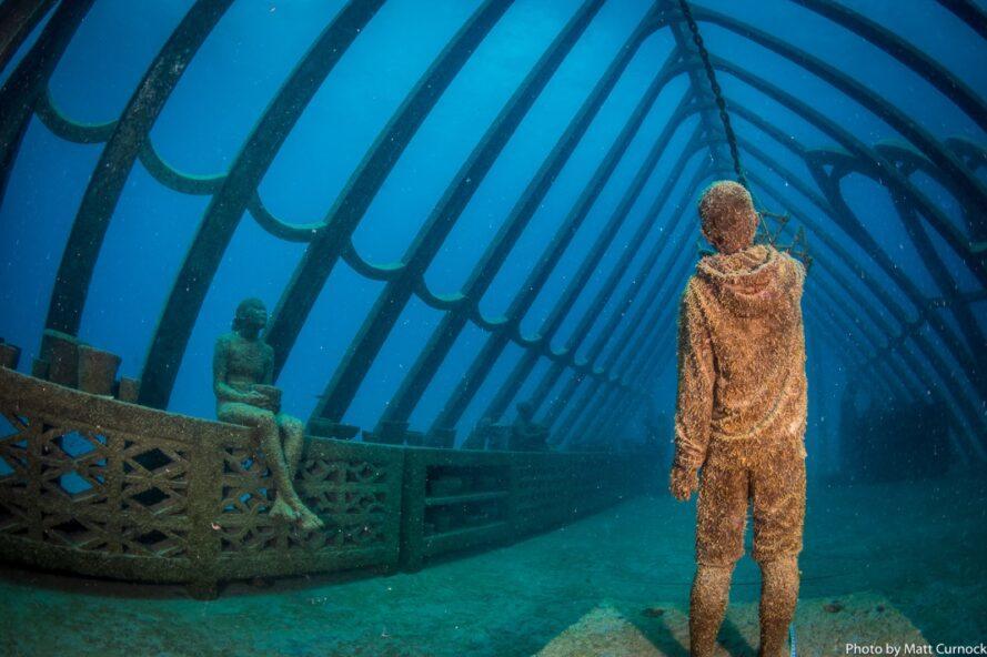 statues de personnes se détendre dans une serre sous-marine
