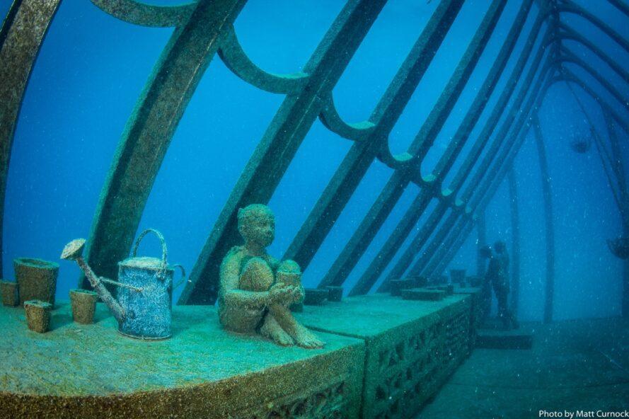 statue d'enfant assis près d'un arrosoir dans une serre sous-marine