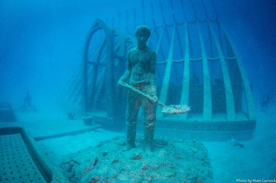 statue de personne avec pelle sous l'eau