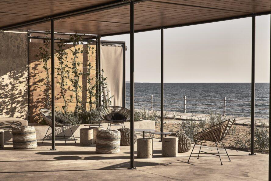 chaises rondes en osier sur un patio couvert face à la mer
