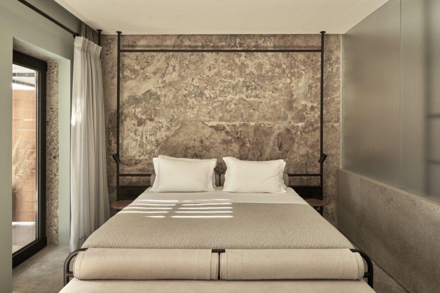 grand lit beige devant un mur de pierre