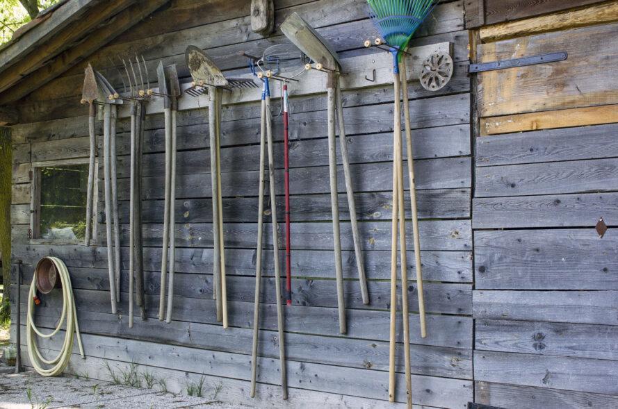 outils de jardin accroché sur le côté d'un cabanon en bois