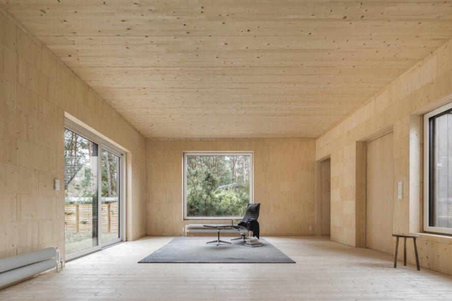 chaise et table foncées et tapis gris dans une pièce en bois clair avec de grandes ouvertures carrées