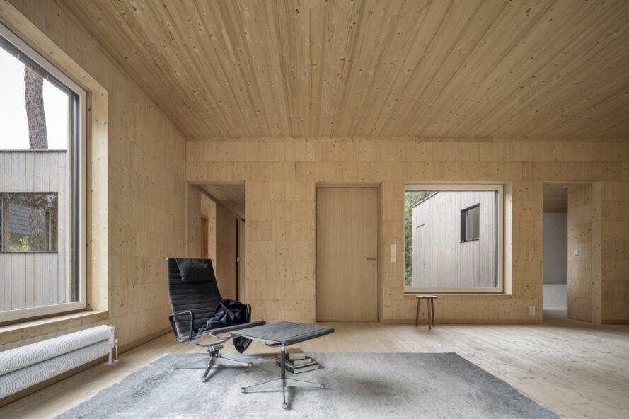 chaise noire et table d'appoint sombre dans une pièce nue avec des murs et des plafonds en bois clair