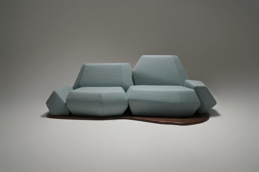 Canapé géométrique bleu clair avec une base en bois courbée sur fond blanc