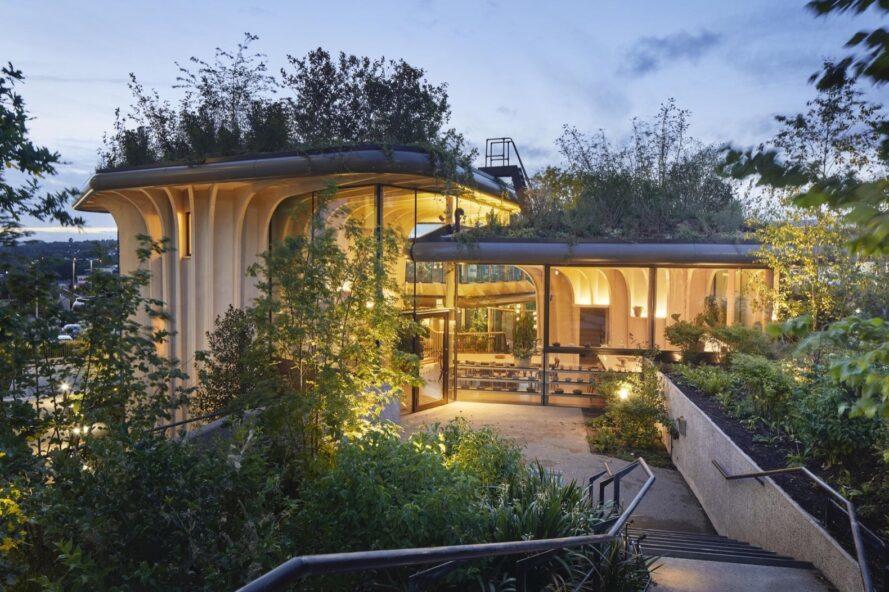 bâtiment à ossature de bois avec des murs en verre et des toits verts luxuriants éclairés de l'intérieur la nuit