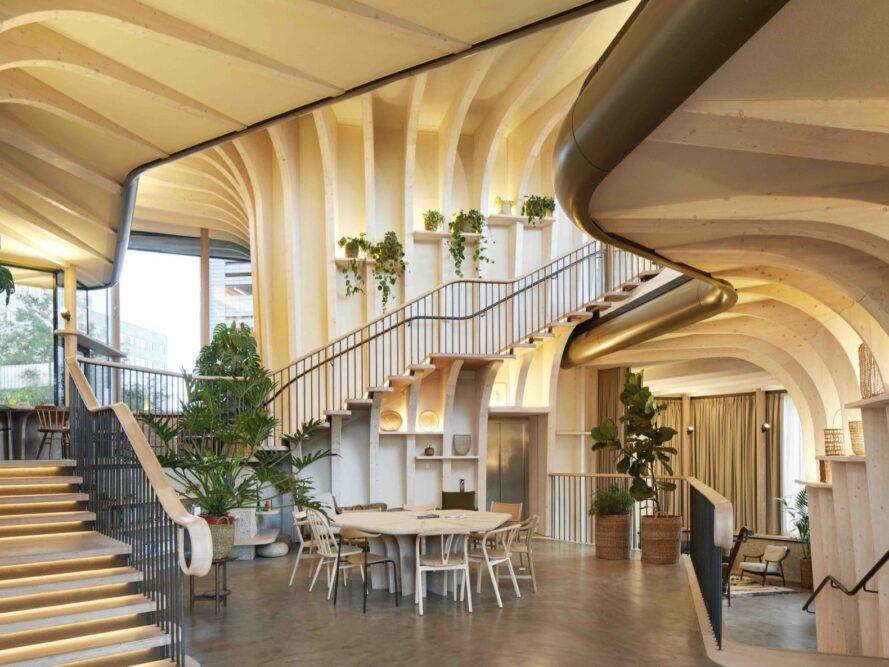 intérieur doublé de bois avec murs courbes, plusieurs plantes et tables et chaises en bois