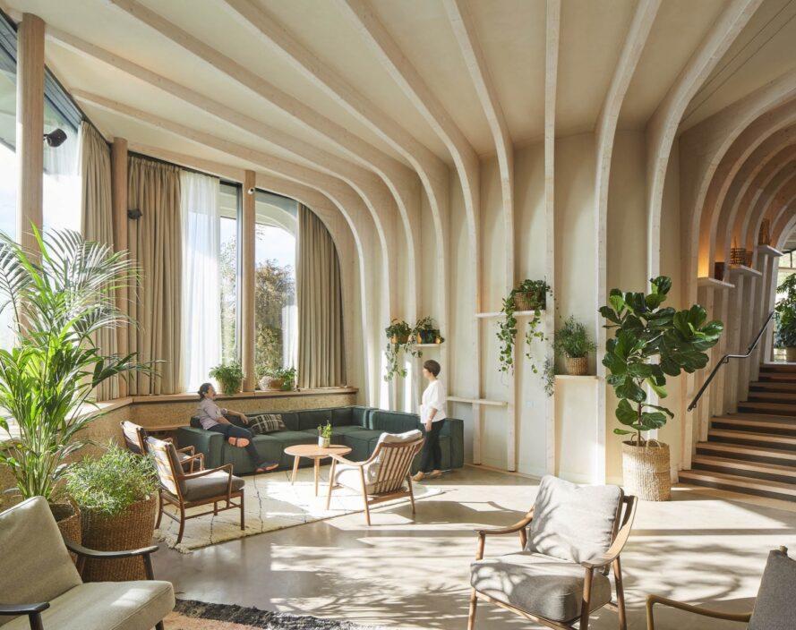Canapé vert et chaises beiges dans une pièce aux murs en bois courbés recouverts de plantes