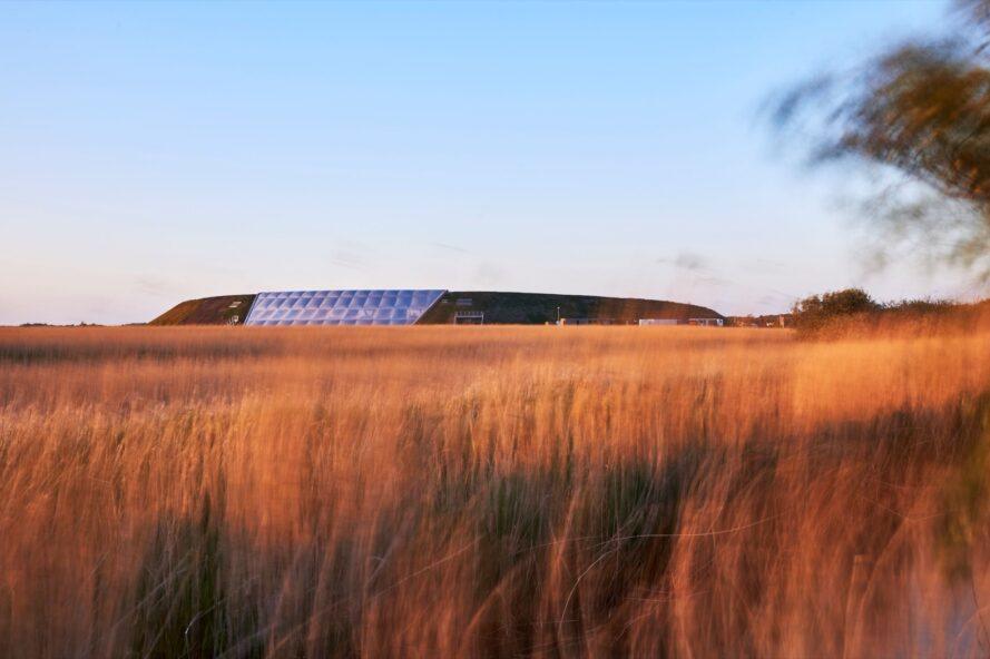 grande colline avec une structure en ETFE blanc intégrée au centre entourée de hautes herbes