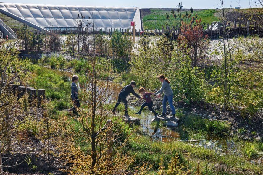 enfants sautant à travers un ruisseau étroit