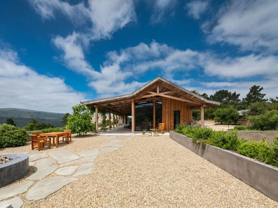 grande cour de gravier en face de la maison en bois avec toit à pignon