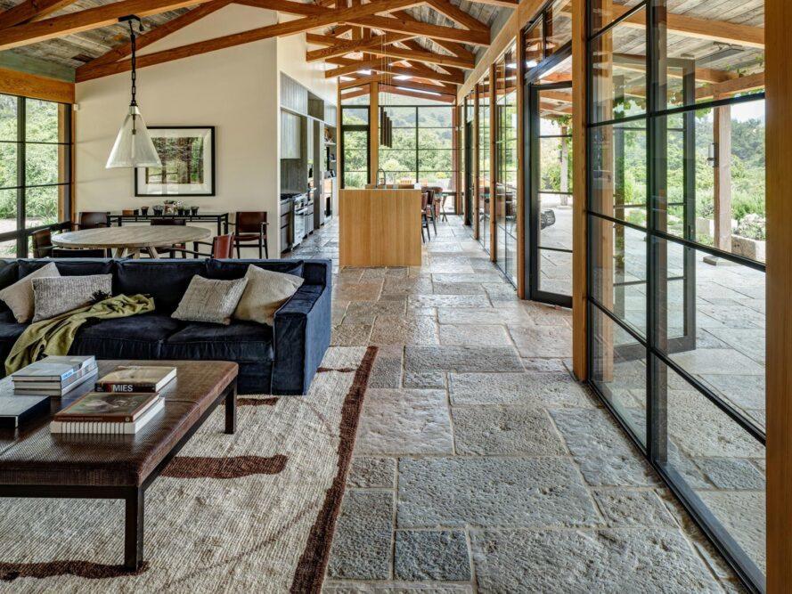 salon avec sols en pierre, poutres apparentes au plafond, canapé bleu marine et table en bois foncé