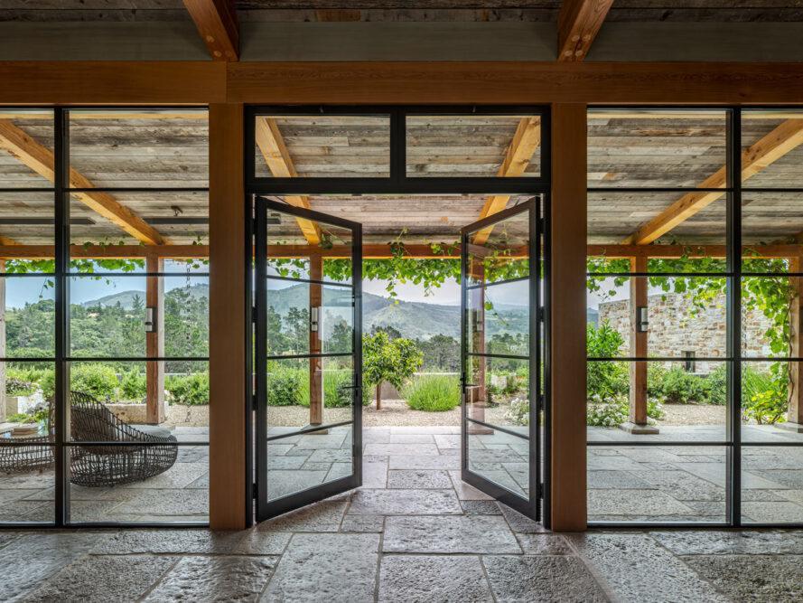 grandes portes vitrées ouvrant sur un patio en pierre couvert