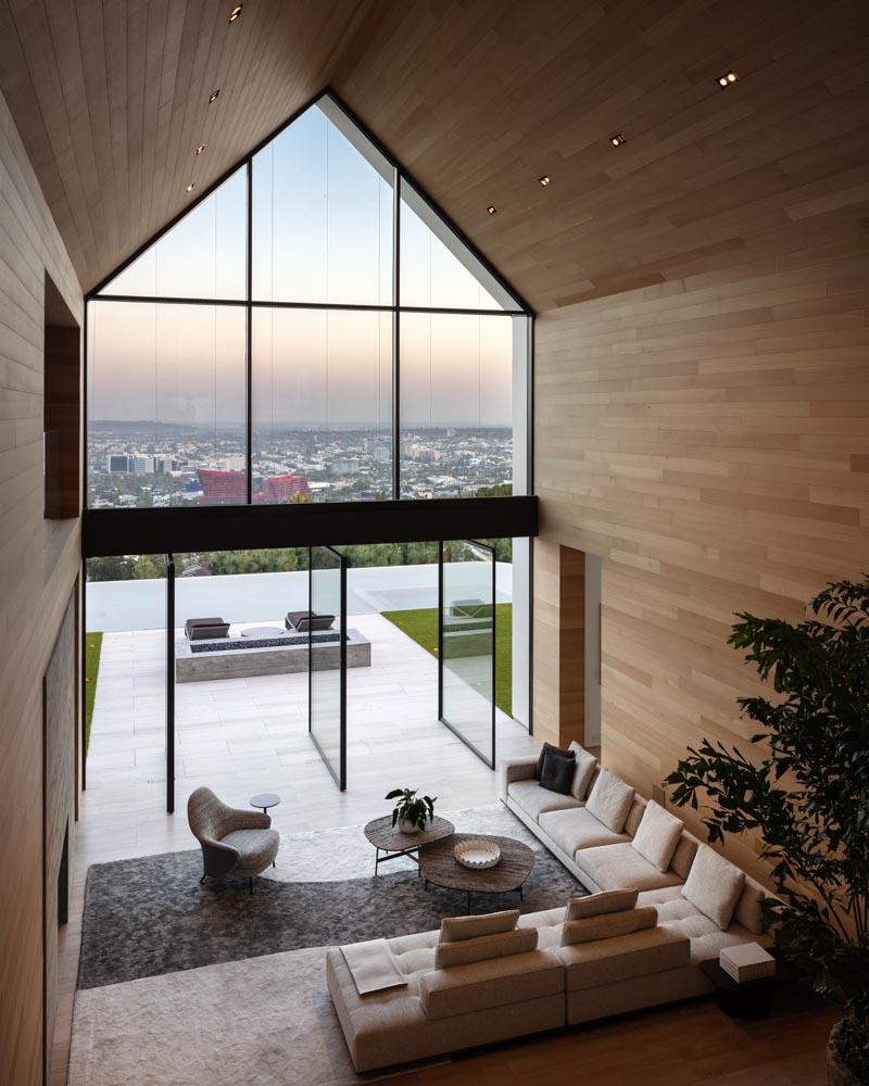 En utilisant des matériaux comme le bois, le béton et la pierre, les concepteurs de cette maison moderne d'inspiration grange ont pu créer un intérieur chaleureux et naturel pour la maison, tandis que les sols en travertin s'étendent de l'intérieur vers l'extérieur.  #GreatRoom #Architecture #GabledCeiling #PivotingDoors