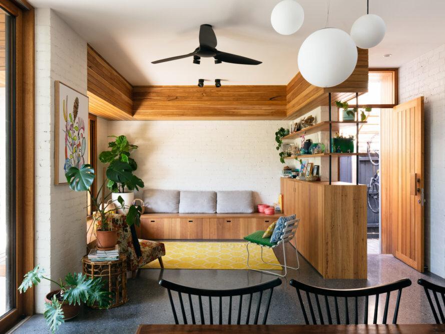 espace de vie avec banc en bois, étagères en bois et beaucoup de plantes