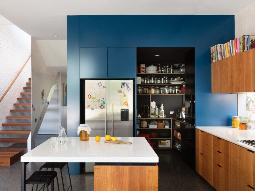 cuisine avec mur bleu, armoires en bois et comptoirs blancs