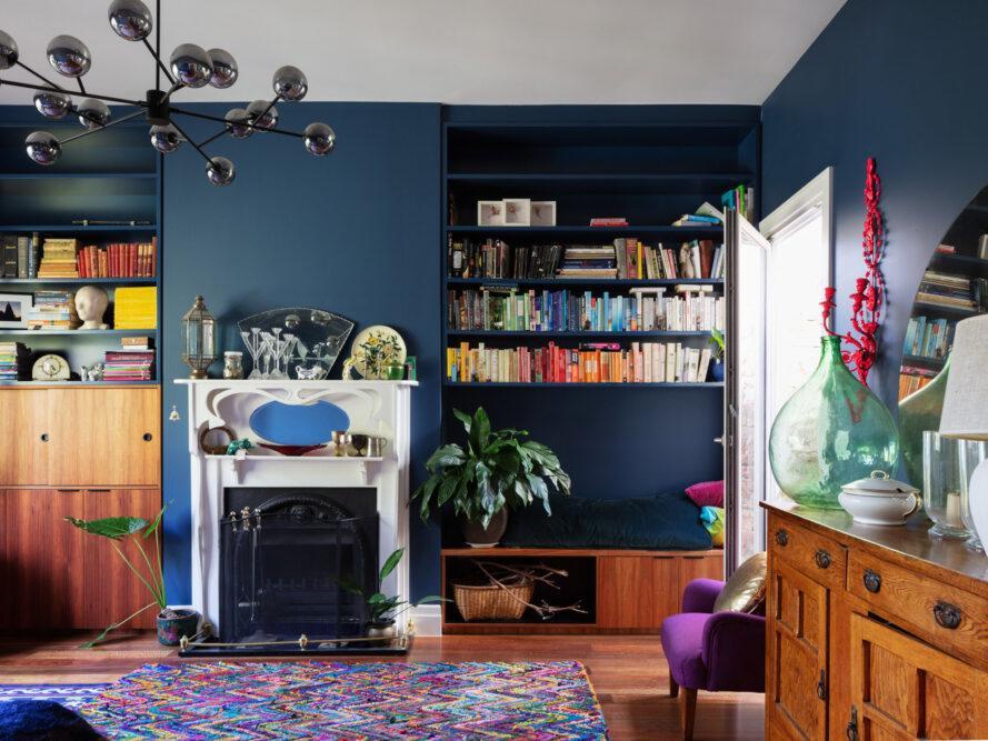 salon avec murs bleu marine, étagères intégrées, petite cheminée blanche et meubles en bois